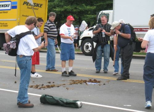 Demonstrators take photos of an Obama sign placed under droppings from a police horse.