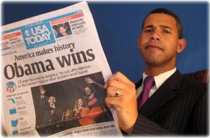 Crosson holding a newspaper headlining election victory for Barack Obama