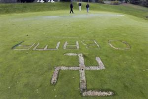 Golfers finish their round on the 18th hole at the Lakeville Country Club, where a swastika was found carved into the green next to President Barack Obama's name on Sunday.