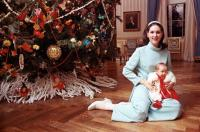 Lynda Bird Johnson Robb in front of White House Christmas tree with infant daughter.