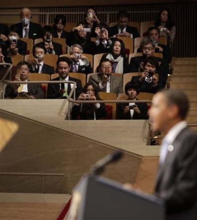 Audience members take pictures of President Barack Obama in Tokyo, Japan