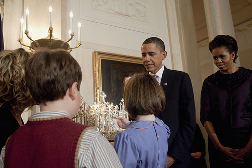 President Barack Obama and First Lady Michelle Obama watch as a child lights the Hanukkah candles