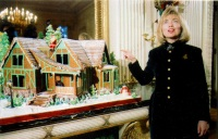 First Lady Hillary Clinton poses with the gingerbread house in 1994