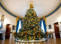 "The ornaments are hung on the tree with blue ribbon embroidered with the words ""reflect,"" ""rejoice"" and ""renew"" in several different languages"