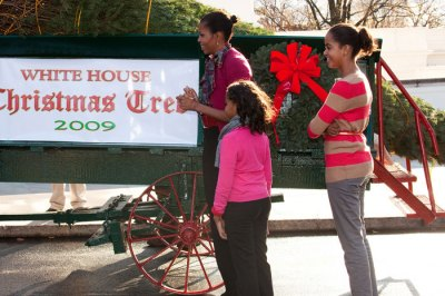 First lady Michelle Obama, with her daughters Sasha and Malia, as they stand with the White House Christmas tree as it is delivered to the North Portico of the White House in Washington, Friday, Nov. 27, 2009.