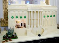 The official White House gingerbread house, designed by White House Pastry Chef Bill Yosses, is displayed in the State Dining Room of the White House during a press preview of holiday decorations in Washington, DC. The replica, made of white chocolate, features a miniature Bo (bottom-C), the Obama's dog, a miniature White House vegetable garden(L) and a view inside to a replica State Dining Room.