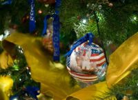 An ornament with the Kennedy Space Center hangs on the official White House Christmas tree in the Blue Room of the White House during a press tour of the holiday decorations