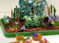 A miniature White House vegetable garden sits alongside the official White House gingerbread house