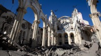 Helicopters fly over the heavily damaged Port-au-Prince Cathedral