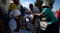 A man carries an elderly woman who needs medical attention in Port Au Prince