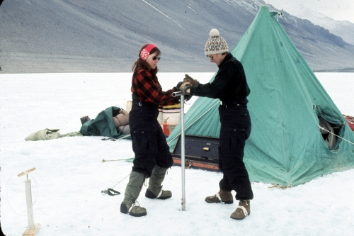 Terry Tickhill (light hat) and Eileen McSaveney (red headband) use a hand augur to drill Lake Vanda, Wright Valley, Antarctica, during the 1969-1970 field season. Water collected during this effort was used to date the lake. The green tent in the background was of the same type as the field crew used for housing during their work in Wright Valley. (Credit: Lois Jones)